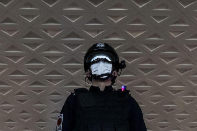 Un policier équipé d'une caméra de lecture thermique et de reconnaissance faciale, àl'aéroport de Wuhan, le 8 avril.