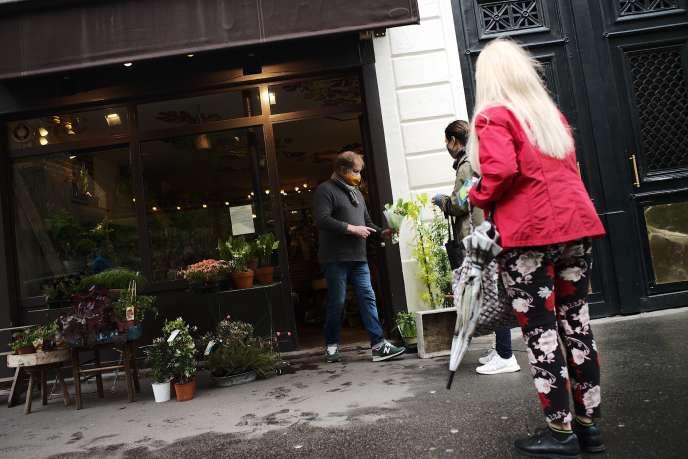 Port du masque, distance de sécurité : un fleuriste et ses clientes mettent en pratique les nouvelles règles de vie sociale, à Paris, le 1er mai.