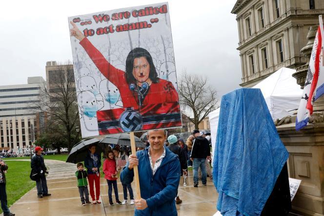 Un manifestant brandit une pancarte montrantGretchen Whitmer grimée en Hitler, à Lansing (Michigan), le 30 avril.
