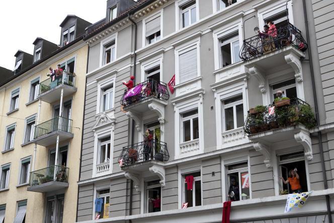 Des habitants à leur balcon tapent sur des casseroles et des poêles le jour de la Fête du travail, à Zurich, en Suisse.
