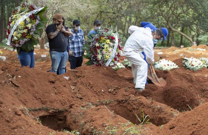 Des employés du cimetière, en combinaison, enterrent des personnes victimes du Covid-19, à Sao Paulo (Brésil), le 30 avril.