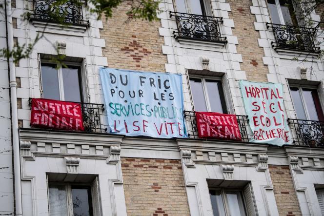 Une banderole portant l'inscription «Du fric pour les services publics»affichée sur un balcon, le jour de la Fête des travailleurs, le 1er mai 2020, à Paris.