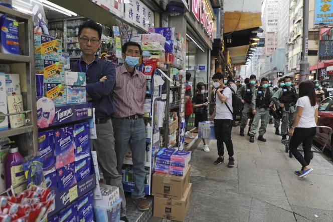 La police antiémeute monte la garde sous les yeux des commerçants lors de la Fête du travail à Hongkong, le vendredi 1er mai 2020.