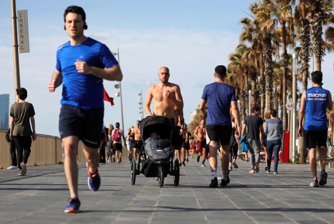 Des passants sur la plage de la Barceloneta pendant le créneau horaire où les sorties sont autorisées pour la première fois depuis le début du confinement, à Barcelone (Espagne), le 2 mai 2020.