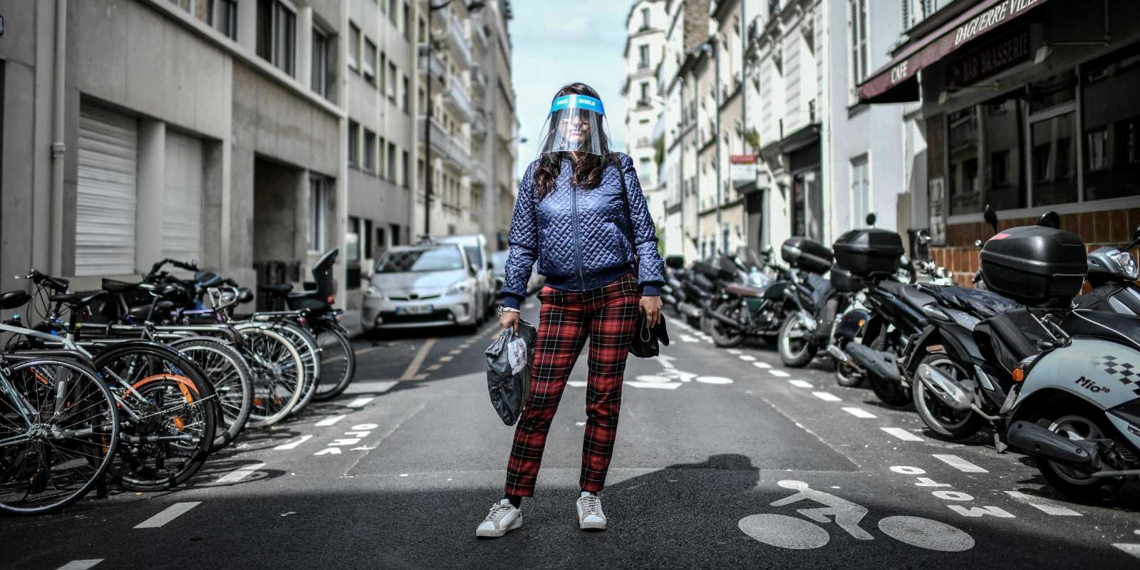 A woman, wearing a protective face shield, poses for a photograph in the streets of Paris on May 4, 2020, on the 49th day of a strict lockdown in France to stop the spread of COVID-19 (novel coronavirus). The French government is also facing fresh criticism over its policies on face masks, which officially went on sale to the public May 4, 2020-- even though people across France have managed to procure them despite the requisition of all stocks and production since March. / AFP / STEPHANE DE SAKUTIN