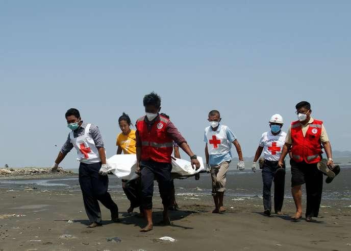 Des membres de la Croix-Rouge transportent le corps d'un conducteur d'un bateau, tué à Sittwe, dans l'État de Rakhine, en Birmanie, le 21 avril.