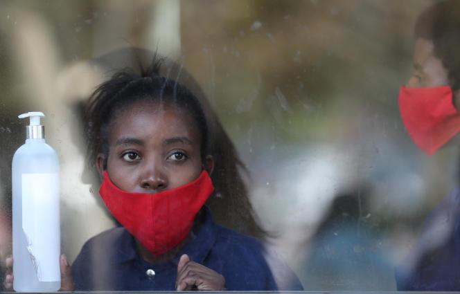 Une employée d'un centre commercial tient un flacon de spray désinfectant, à Soweto, en Afrique du Sud, le 5mai.