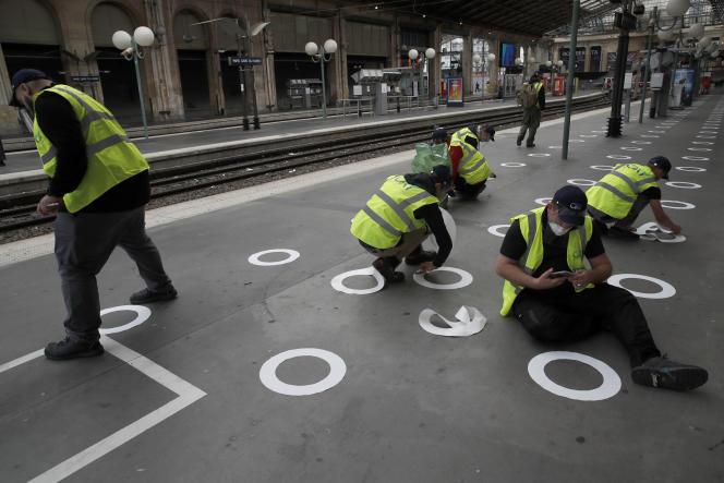 Des cercles en plastique sont collés sur le sol afin de respecter les distances sociales, à la gare du Nord, à Paris, le 4mai.