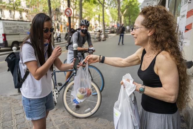 Justine, une cuisinière, remet les paniers repas qu'elle vient de préparer à Mélissa, livreuse bénévole à Paris.