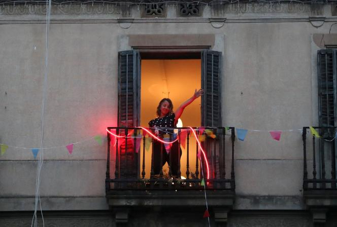 Une résidente de Barcelone danse depuis son balcon, pendant le confinement mis en place pour enrayer l'épidémie de Covid-19, le 17 avril.