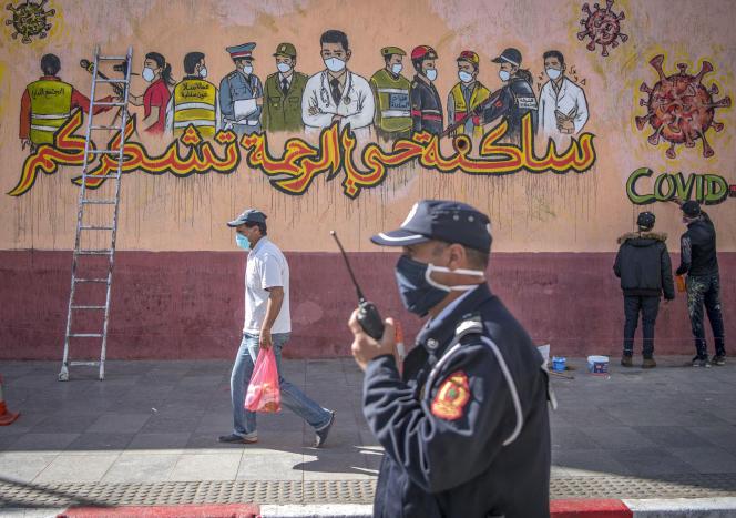 Un policier passe devant une fresque murale remerciant les travailleurs mobilisés pendant l'épidémie liée au coronavirus, à Salé, au Maroc, le 26avril 2020.