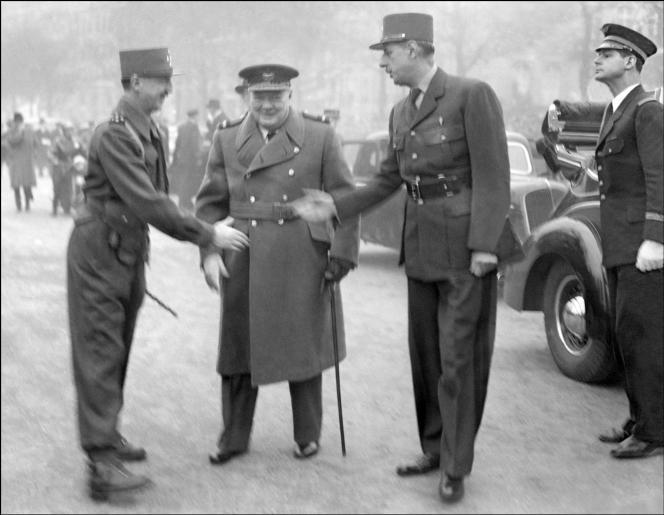 Le général Pierre Koenig et le général Charles de Gaulle se serrent la main en présence du premier ministre britannique, Winston Churchill, lors des cérémonies du 11novembre 1944, à l'Arc de Triomphe, à Paris.