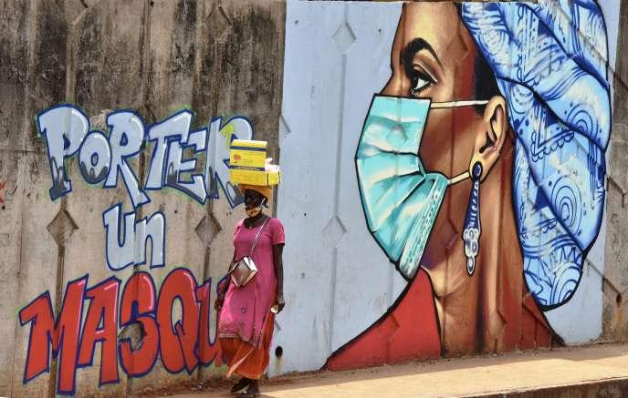 Une femme passe devant une fresque murale sensibilisant aux gestes barrières anti-coronavirus, à Conakry, en Guinée, le 4mai 2020.