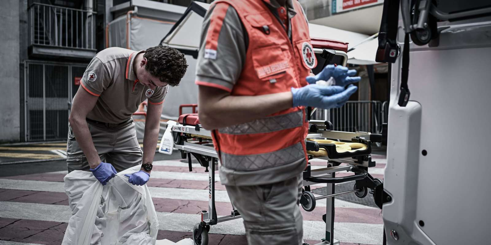 A Red Cross volunteer removes a protective suit outside an hospital after an intervention at the home of a woman with symptoms of Covid-19 during the Red Cross operations to enforce the SAMU (French Urgent Medical Aid Service) on May 5, 2020, in Paris, during the lockdown in France aimed at curbing the spread of the COVID-19 disease, caused by the novel coronavirus. / AFP / PHILIPPE LOPEZ