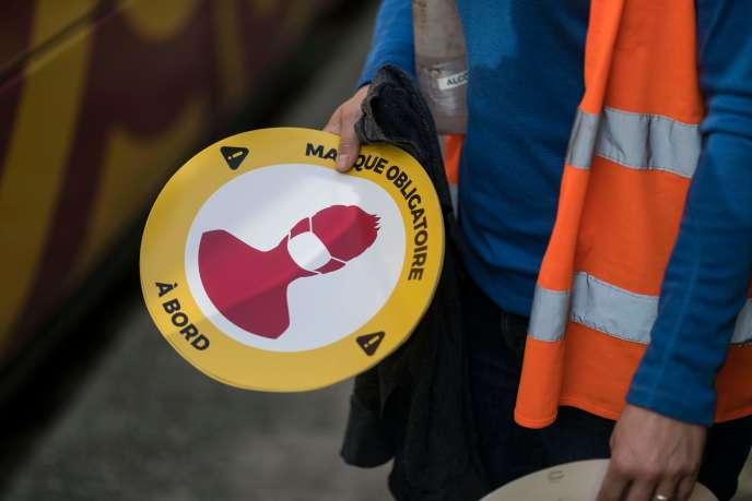 Un employé tient des autocollants indiquant «masque obligatoire à bord» au dépôt de bus Solea à Mulhouse, le 8 mai.