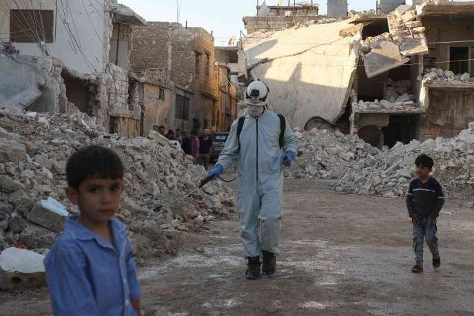 Un membre des Forces de la défense civile syrienne désinfecte un quartier détruit par des bombardements à Atareb (Syrie), le 7 mai.