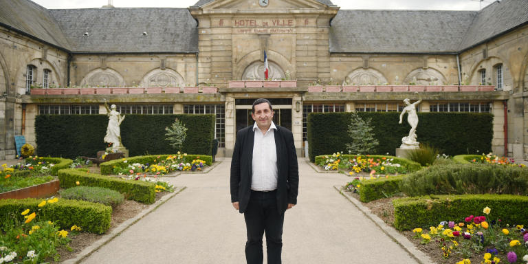Newly elected Communist mayor of Stains Azzedine Taibi poses on April 3, 2014 in front of the city hall in Stains, outside. AFP PHOTO MARTIN BUREAU (Photo by MARTIN BUREAU / AFP)
