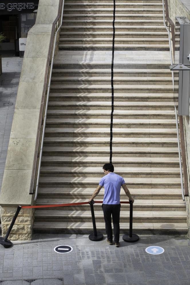 La promenade Sainte-Catherine est un espace commercial privé a ciel ouvert: l'assistant technique colle une bande de scotch noir au milieu du grand escalier pour mettre en place un sens de circulation, le 7 mai.