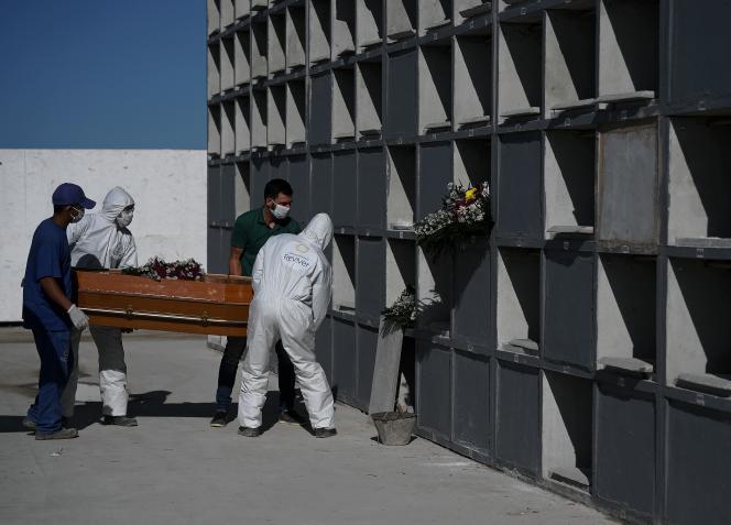 Les employés d'un cimetière de Rio disposent d'un cercueil d'un mort du Covid-19, le 9 mai.