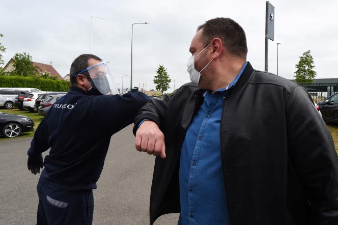 Un concessionnaire automobile portant une visière et un masque accueille un client, à Illiers-Combray (Eure-et-Loir), le 4 mai.
