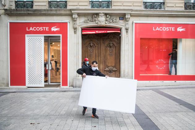 Après cinquante-cinq jours de confinement, les Champs-Elysées se réveillent lentement. Au numéro95 de l'avenue, l'équipe de la marque Lacoste remballe à la hâte les vêtements d'hiver, décroche les kakémonos de la vitrine et passe l'aspirateur. Le kiosquier voisin, lui, n'attend«rien»de cette journée: «La clientèle n'est pas là», explique-t-il, en évoquant«les bureaux qui sont tous en télétravail»et cette clientèle touristique qui fait défaut à Paris depuis la fin janvier.