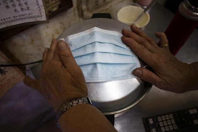 Pour limiter les risques de transmission du virus, la gérante d'un petit restaurant chauffe son masque sur la marmite à riz, afin de détruire de potentiels microbes.
