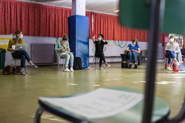 A Saint-Martin-d'Hères, dans la banlieue au sud-ouest de Grenoble, la rentrée se prépare à l'école Paul-Langevin, un établissement prioritaire (REP+) de 167élèves sur dix classes. Une quarantaine d'élèves doivent reprendre la classe dès mardi12. Sur onze enseignantes, neuf seront là chaque jour, ce qui permet d'éviter d'« alterner» les groupes comme ce pourra être le cas ailleurs. Cette journée de «prérentrée», inhabituelle en cette saison, est consacrée aux «gestes barrières» et à la préparation des locaux. Les enseignantes se sont réunies, lundi matin, dans la sallede motricité où se déroulent d'habitude les activités physiques: la salle de réunion habituelle est trop petite pour respecter la distanciation physique.