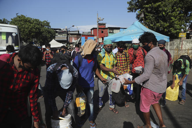 Distribution de nourriture à des travailleurs migrants venus d'autres états du pays et coincés sans ressources depuis le début de confinement dans un bidonville proche de la gare de Bombay, le 11 mai.