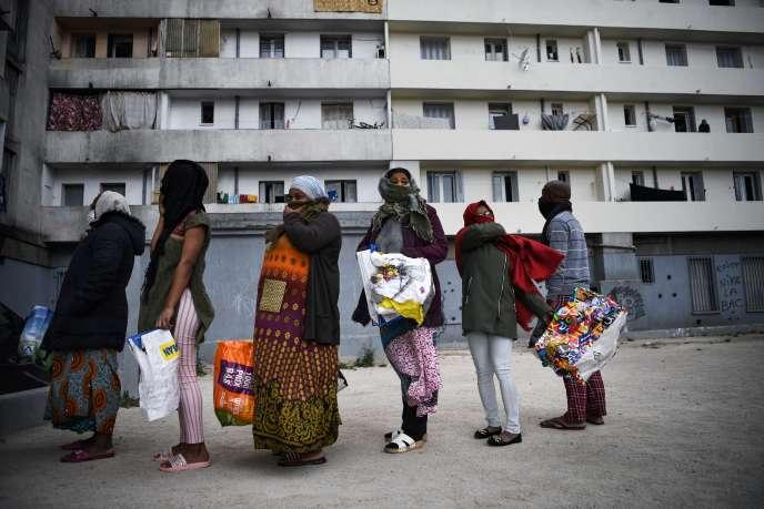 Des habitants font la queue au bas de leur immeuble pour aller chercher de la nourriture lors d'une distribution organisée par un groupe de voisins, le 31 mars 2020, à Marseille.
