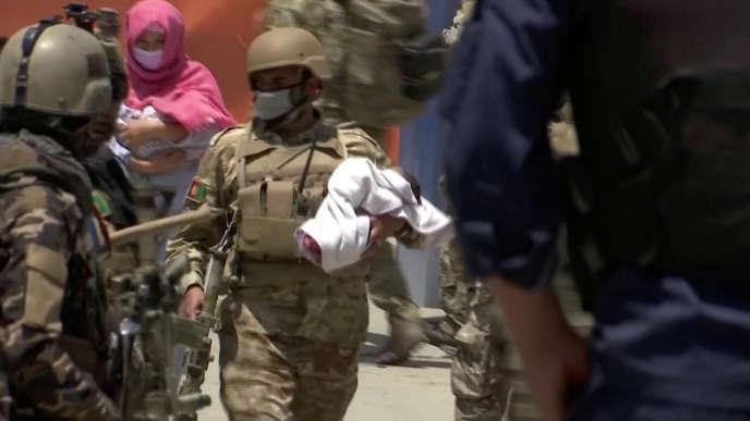 Des agents de sécurité évacuent un bébé de l'hôpital Dasht-e-Barchi lors d'une attaque terroriste, le 12 mai, à Kaboul.