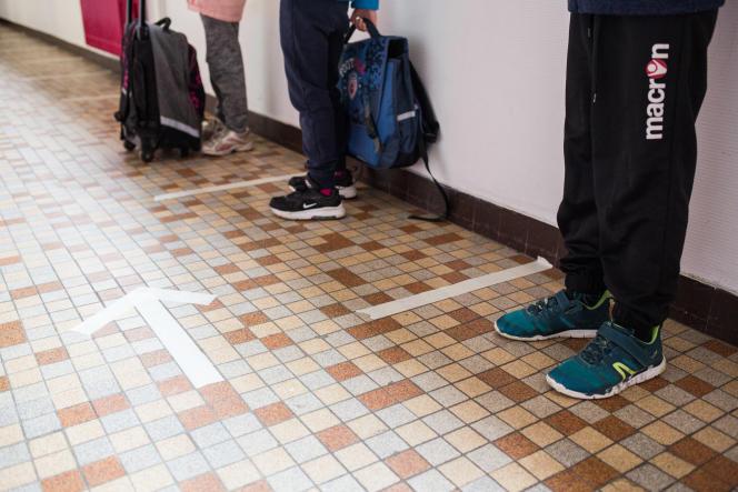 Les élèves attendent avant d'aller se laver les mains pour entrer dans leur classe.