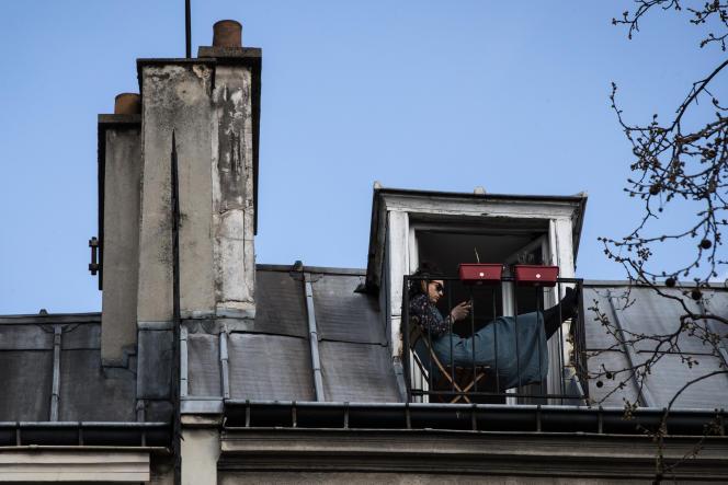Une jeune femme consulte son téléphone sur son balcon, le 18 mars à Paris.