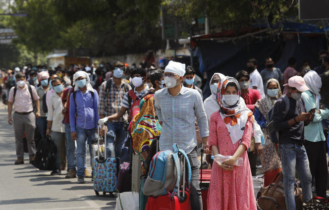 Des habitants de New Delhi dans une file d'attente, masque sur le visage, afin de limiter les risques de propagation du virus.