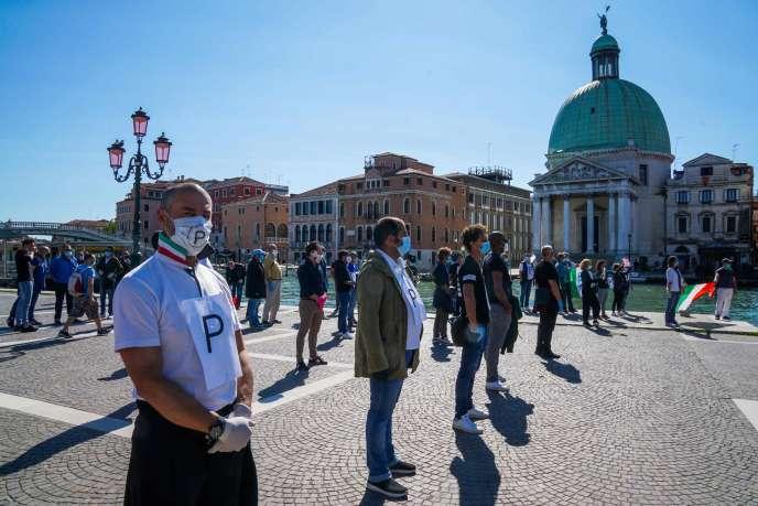 Des commerçants réclament la réouverture des commerces lors d'un flashmob près de la gare de Venise-Santa-Lucia, le 4 mai.
