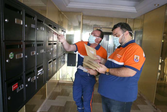 Des membres de la Protection civile distribuent des masques de protection dans les boîtes aux lettres des habitants d'Ajaccio (Corse-du-Sud), le 7 mai.