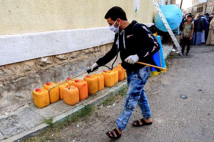 Un volontaire stérilise des jerricans d'eau dans la rue. à Sanaa, le 14 mai.
