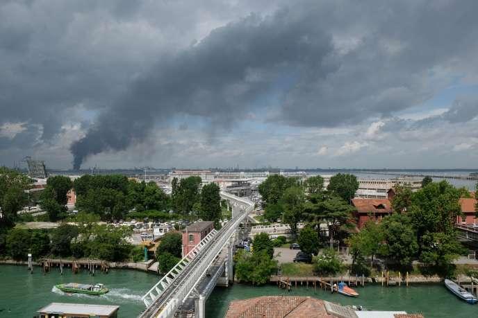 Une épaisse fumée noire s'échappe de l'usine chimique où s'est déclaré un incendie, vendredi 15 mai, vu de Venise.