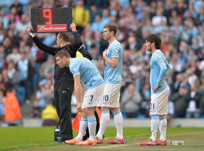 Trois joueurs de Manchester City, James Milner, Edin Dzeko et David Silva, se préparent pour un triple remplacement lors d'un match contre l'équipe deWigan Athletic, le9mars2014.
