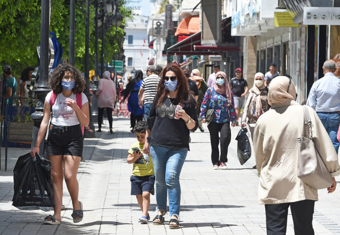 Des Tunisiens se promènent sur l'avenue Habib-Bourguiba, en plein coeur de Tunis, le 12 mai 2020, à la suite de l'assouplissement du confinement.