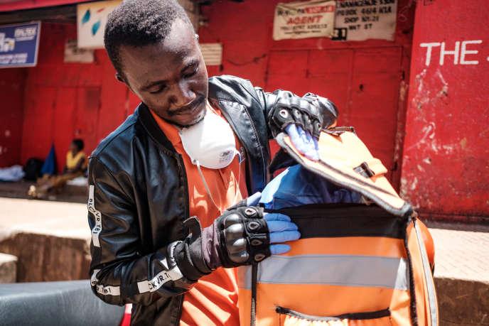 Un employé ougandais de la plate-forme de livraison à domicile Jumia vient chercher une commande au marché de Nakasero, à Kampala, le 1eravril 2020.