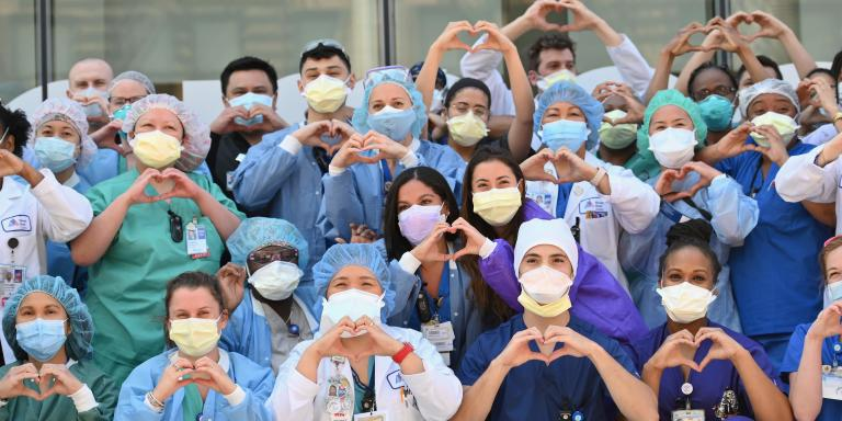 Nurses and healthcare workers gesture hearts in celebration of Nurse Week and International Nurses Day outside Mt. Sinai Oueens in the Queens borough of New York City on May 12, 2020. / AFP / Angela Weiss