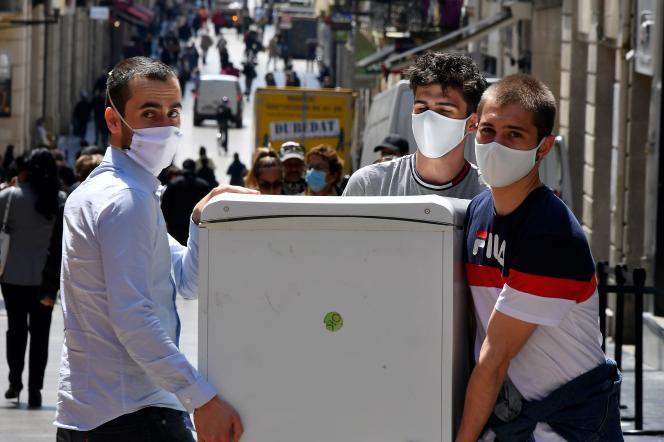 Des gens masqués transportent un réfrigérateur, à Bordeaux, le 15 mai 2020.