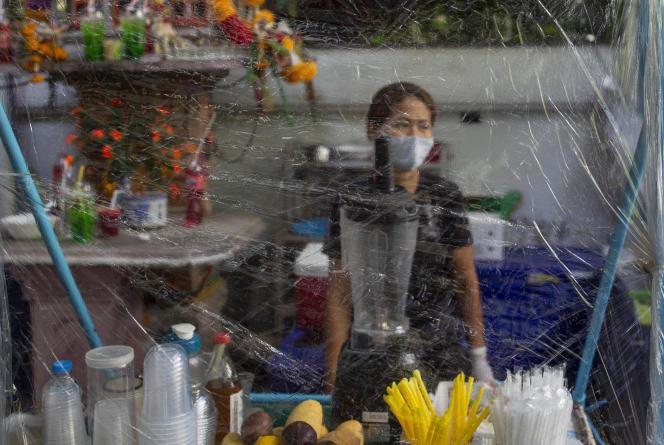 Une vendeuse a protégé son stand de nourriture par un rideau plastifié, dans une rue de Bangkok, le 13 mai.