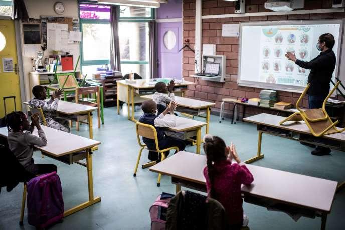 Un enseignant montre à ses élèves comment se laver efficacement les mains, dans une école primaire deLa Courneuve (Seine-Saint-Denis), le 14 mai.