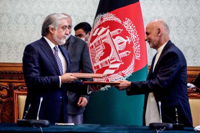 Le président afghan Ashraf Ghani (à droite) et son rival Abdullah Abdullah (à gauche) échangent des documents officiels consacrant leur accord de partage du pouvoir, le 17mai 2020, au palais présidentiel, à Kaboul. Photographie transmise par le cabinet présidentiel.
