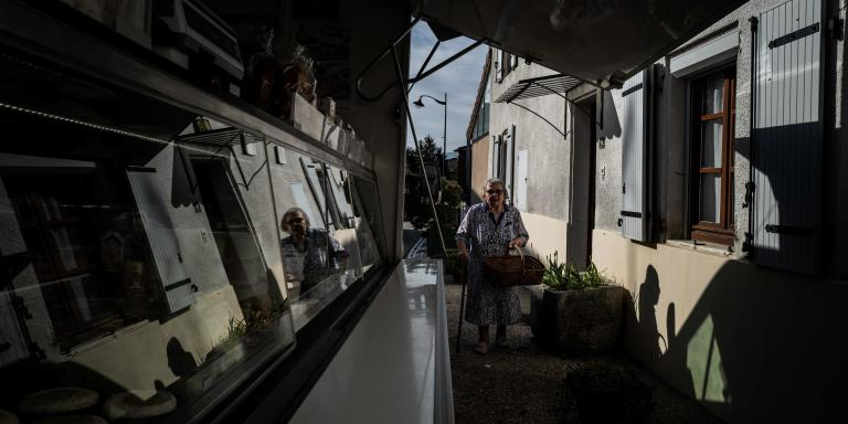 An elderly woman leaves her home to buy supplies to French ambulant grocer Claude Mottet during his daily tour to deliver food to his clients around Romans-sur-Isere on April 17, 2020, during a strict lockdown across France aimed at curbing the spread of the COVID-19 pandemic, caused by the novel coronavirus.  / AFP / JEFF PACHOUD