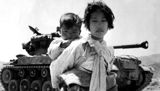 Une jeune Coréenne porte son frère, en juin1951, avec en arrière-plan un char M26 immobilisé, à Haengju, en Corée.