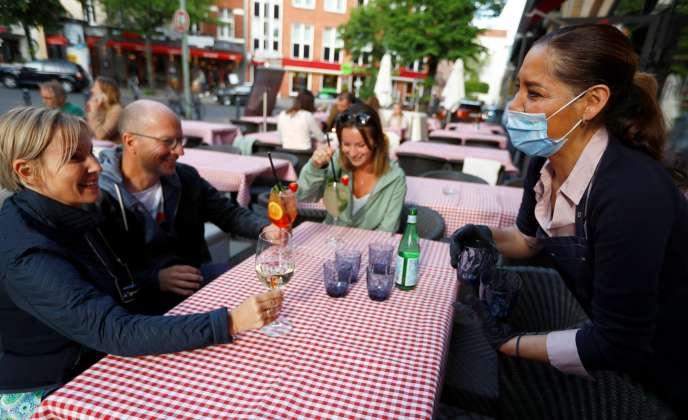 Une serveuse du restaurant Petrocelli porte un masque face à des clients, à Berlin, le 16 mai.