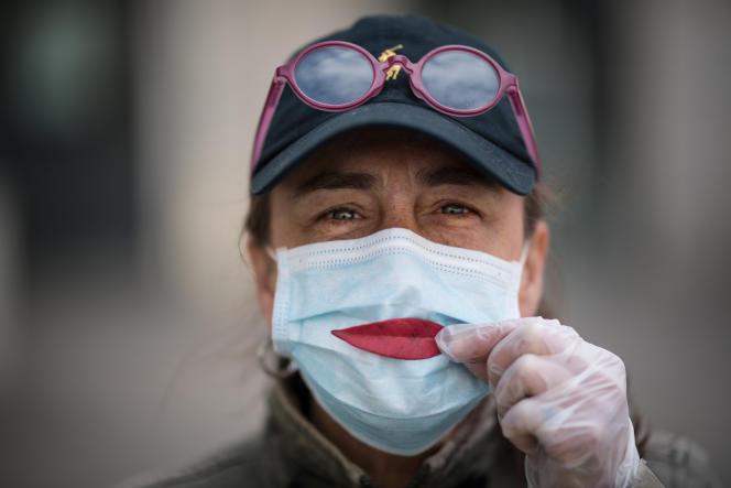 Une femme pose une feuille d'arbre sur son masque en guise de sourire, à Nantes (Loire-Atlantique), le 29 mars.