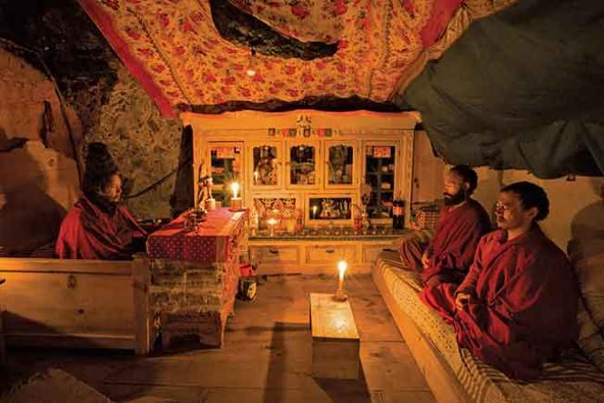 A l'intérieur de la grotte, les disciples et le maître méditent à la lueur de la bougie.